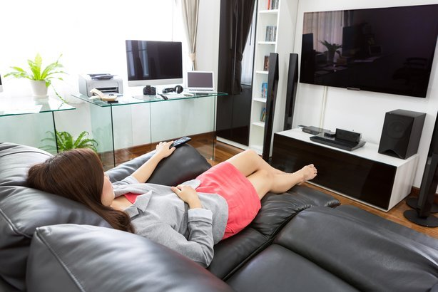 business woman watching tv in modern home office with computer and laptop
