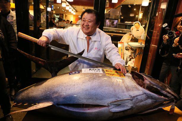 Kiyoshi kimura, president of Kiyomura K.K, poses for photos with a 180.4 kilograms (397 pounds) fresh tuna after this year's first auction at Tsukiji Market