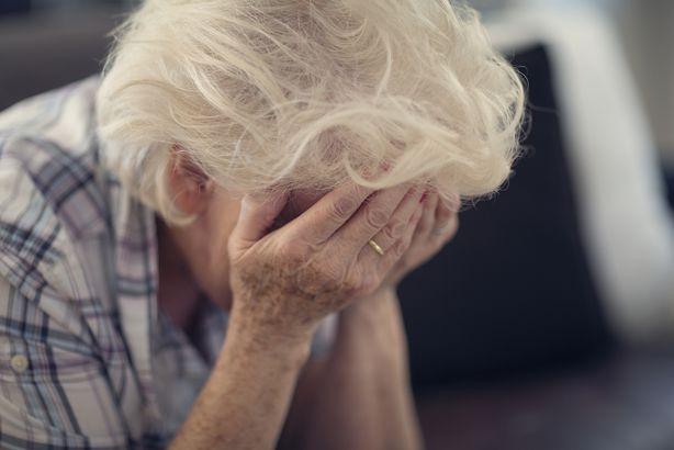 senior woman holding head in hands in despair