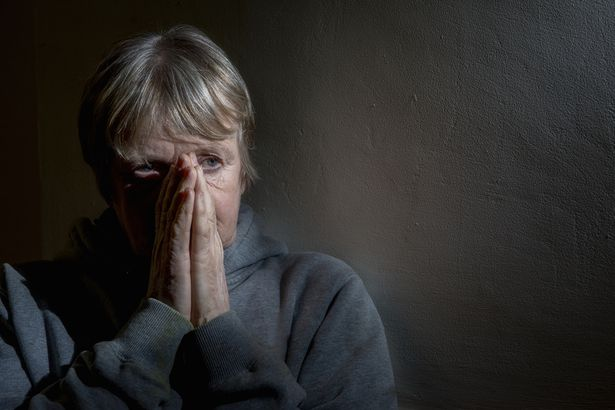 senior woman upset and worried in the darkness