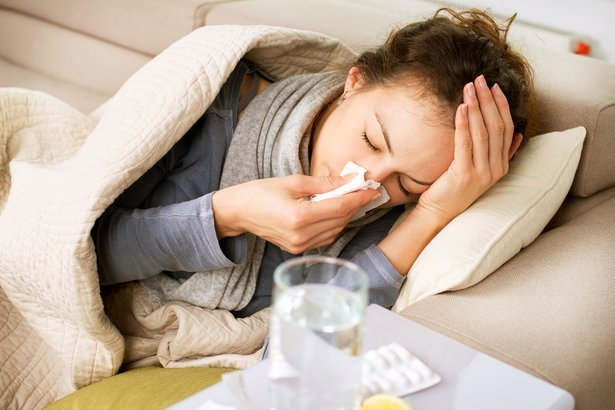 sick woman sneezing into tissue while in bed