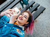 Teenage girl lying on a bench outside using smart phone