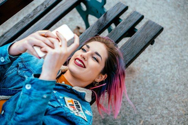 Teenage girl lying on a bench outside using smart phone