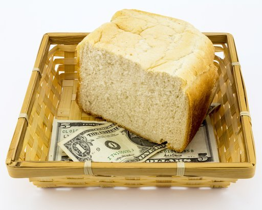 5 and 1 dollar notes with half a loaf of white bread in basket
