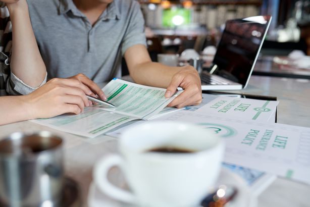 couple at coffee shop studying life insurance brochure