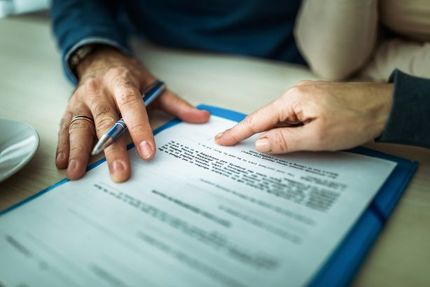 person about to sign legal document with hand pointing