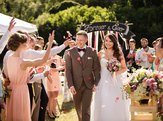 bride and groom after wedding ceremony with guests showering them with rose petals down the aisle
