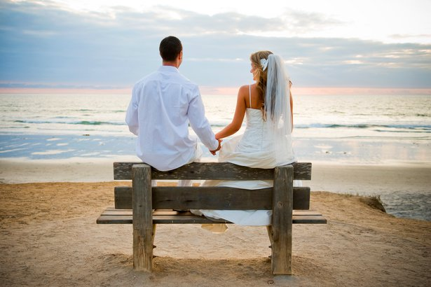 Woman in a wedding dress with man sitting on a bench on the beach