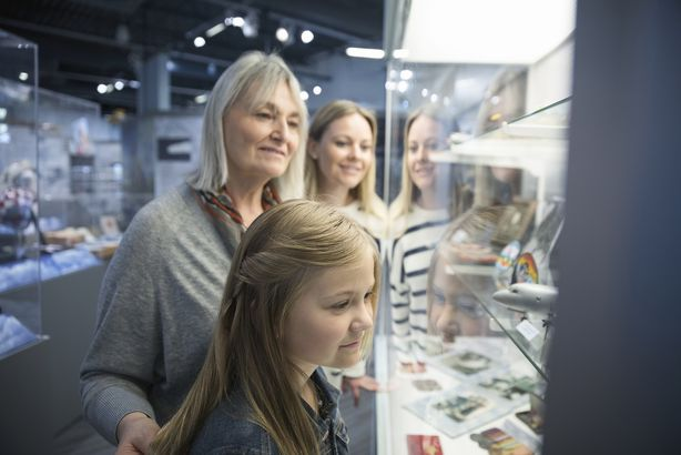 female multi-generation family looking at exhibit artifacts in war museum