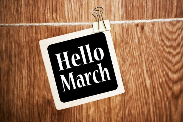 'Hello March' text written on a chalkboard with a wood wall background
