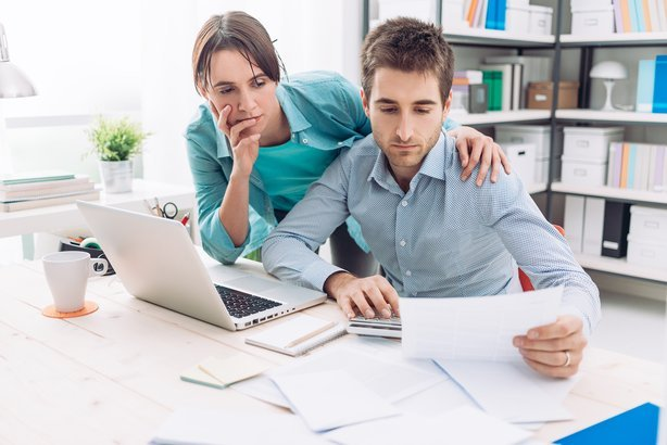 couple at home checking expensive bills at desk