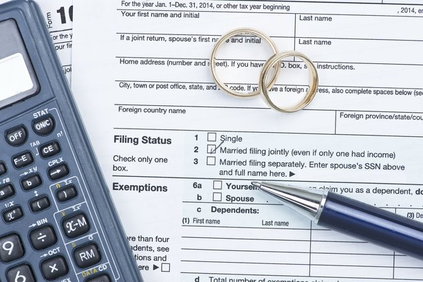 wedding rings with United States tax form 1040 and pen and calculator
