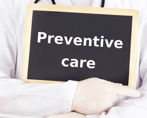 doctor holding blackboard with 'Preventive Care' on it