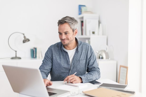 smiling grey hair man with beard working on laptop in home office