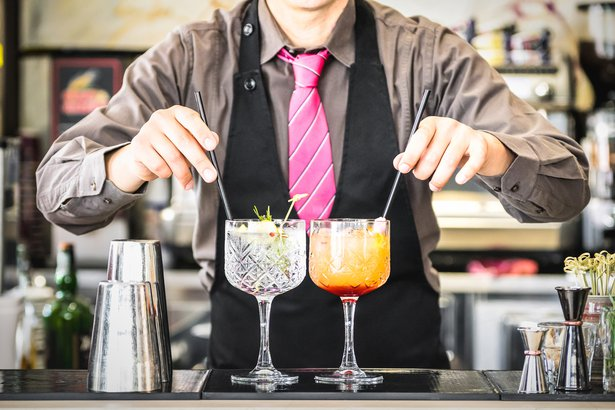 classic bartender serving gin tonic and tequila sunrise with straw on drink glasses cups at fashion cocktail bar