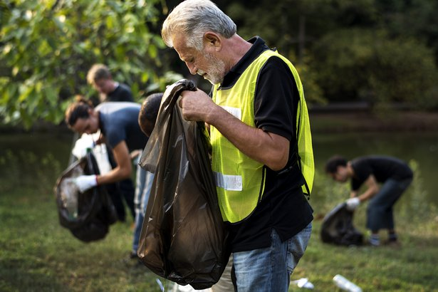 senior man cleaning up park with volunteer group
