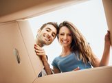 smiling young couple opening a carton box and looking inside