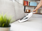 Vacuuming the couch with a hand-held vacuum.