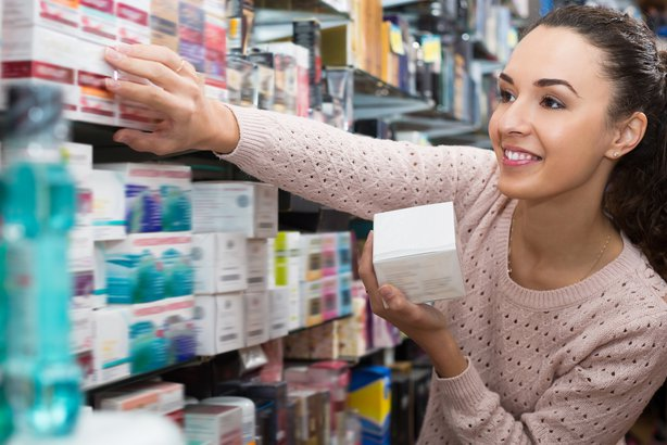 young woman selecting skincare in store