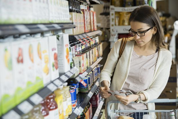 woman shopping with coupons at grocery store