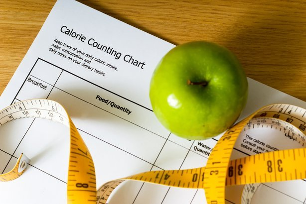 calorie counting chart, green apple and tape measure