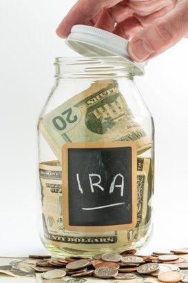 hand opening lid of glass jar with black chalk 'IRA'