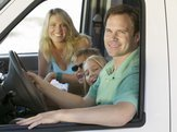 family sitting in the front of an RV on vacation