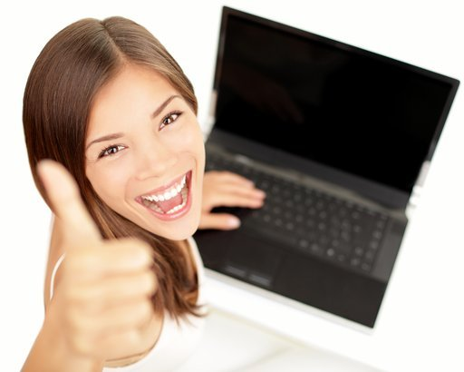 happy woman giving thumbs up sitting at laptop with excited face expression