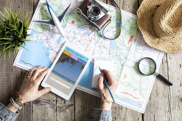 Aerial view of woman planning vacation with a map and tablet