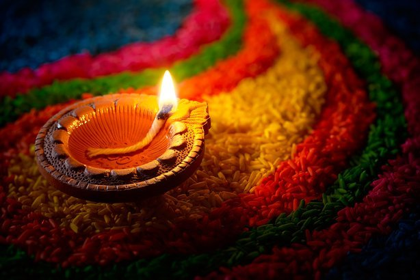 traditional diya lamp lit on colorful rangoli