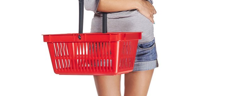 surprised casual young woman standing smiling with empty shopping cart basket