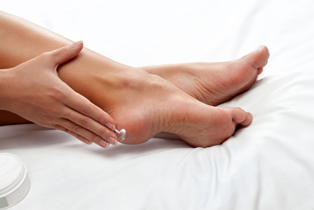 Woman applying lotion to her heel
