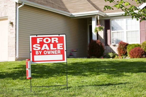 home with 'For Sale By Owner' sign in front yard