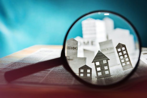 Magnifying glass looking at paper houses and condo buildings