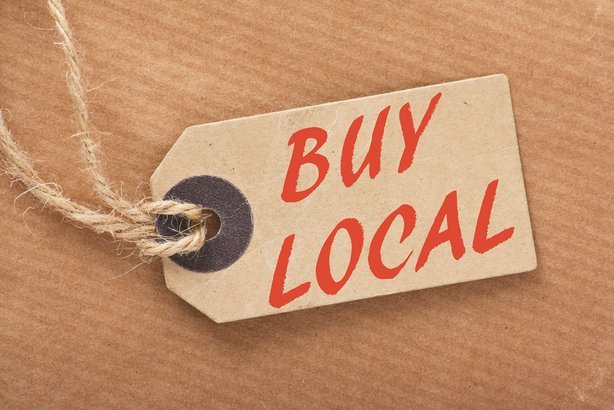 'Buy Local' written on a brown paper price tag