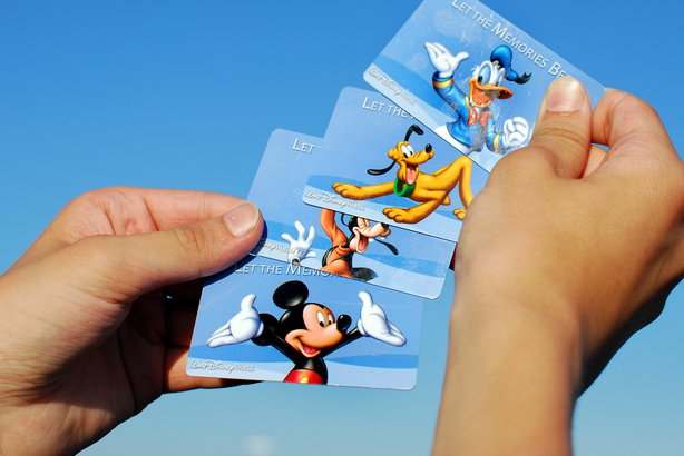 Hands holding up Disney theme park tickets