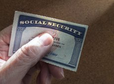 Hand holding social security card with thumb over the number