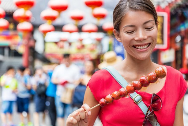 woman eating traditional Chinese food snack from Beijing