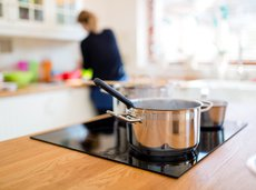 Closeup of pan on burner with woman in the background