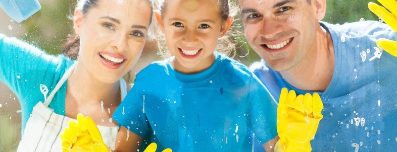 happy young family of three cleaning home window glass together