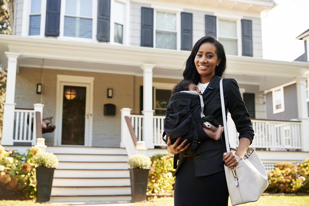 Mom standing outside of her home ready to go to work with baby on her chest
