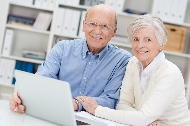 senior couple working on a laptop in an office sitting close together as they share the screen