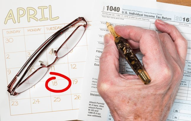 senior hand with pen on tax return form with calendar and glasses in the background