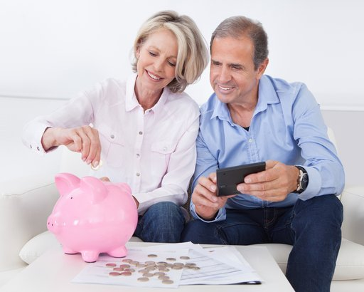 happy mature couple calculating coins in the piggybank