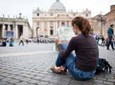 Woman sitting outside of St. Petersburg Square using a map