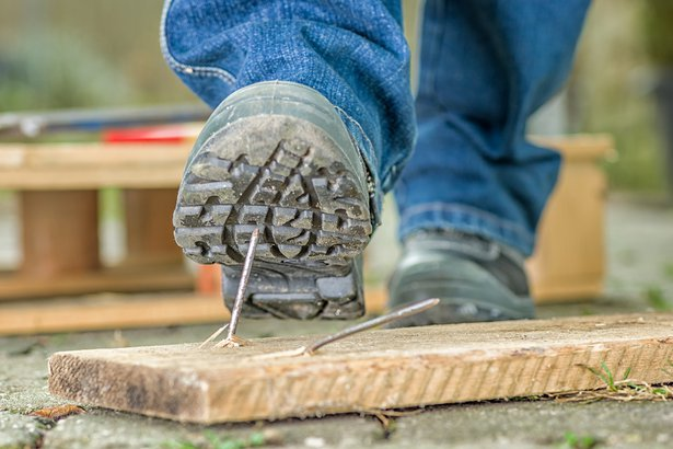 worker in safety boots about to step on a nail