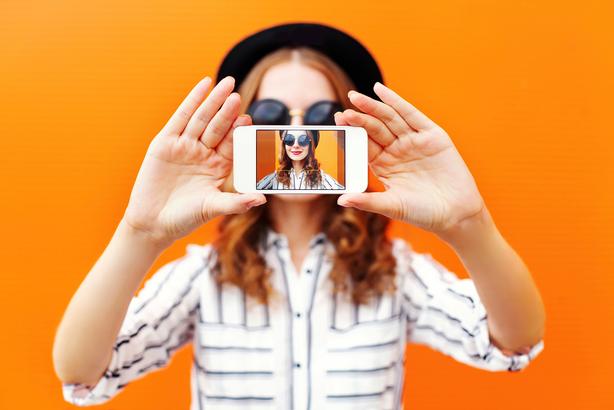 Woman taking a selfie with an orange backdrop