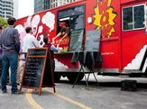 customers wait in line to order meals from a popular food truck during their lunch hour