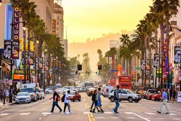 traffic and pedestrians on Hollywood Boulevard at dusk in Los Angeles