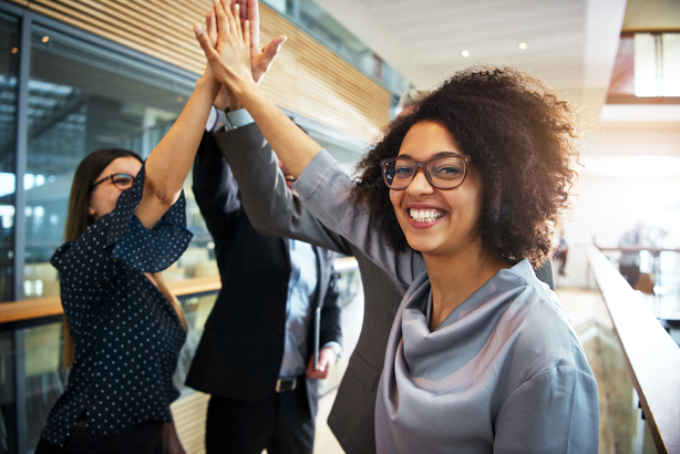 Happy employee smiling and giving high-five to other employees